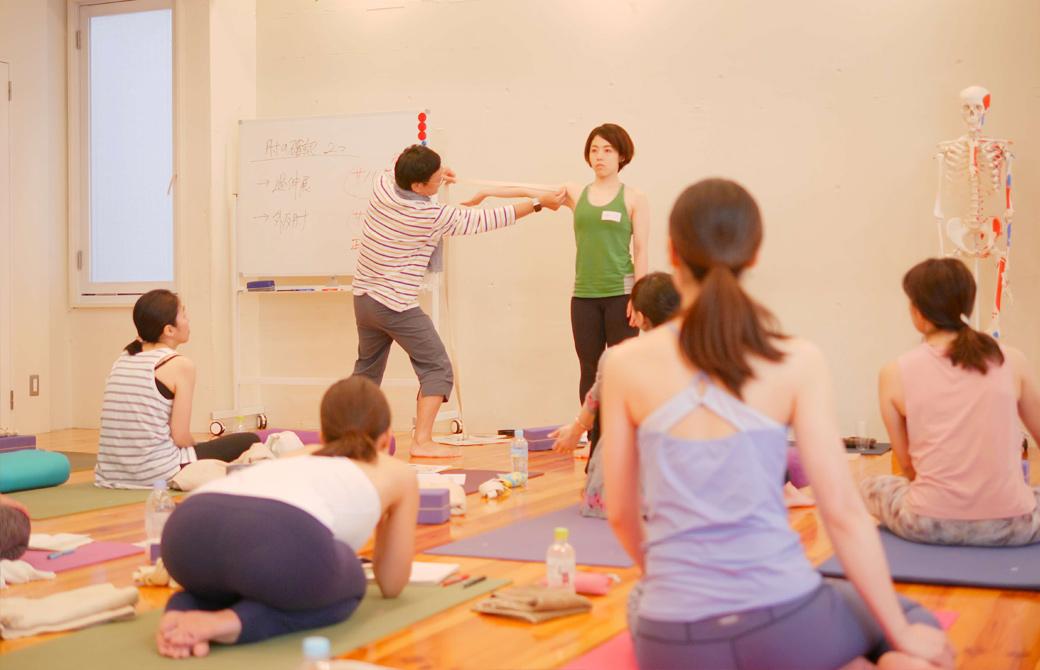 内田かつのり先生が生徒さんの広げた腕にベルトをあてて肘の過伸展をチェックしている様子