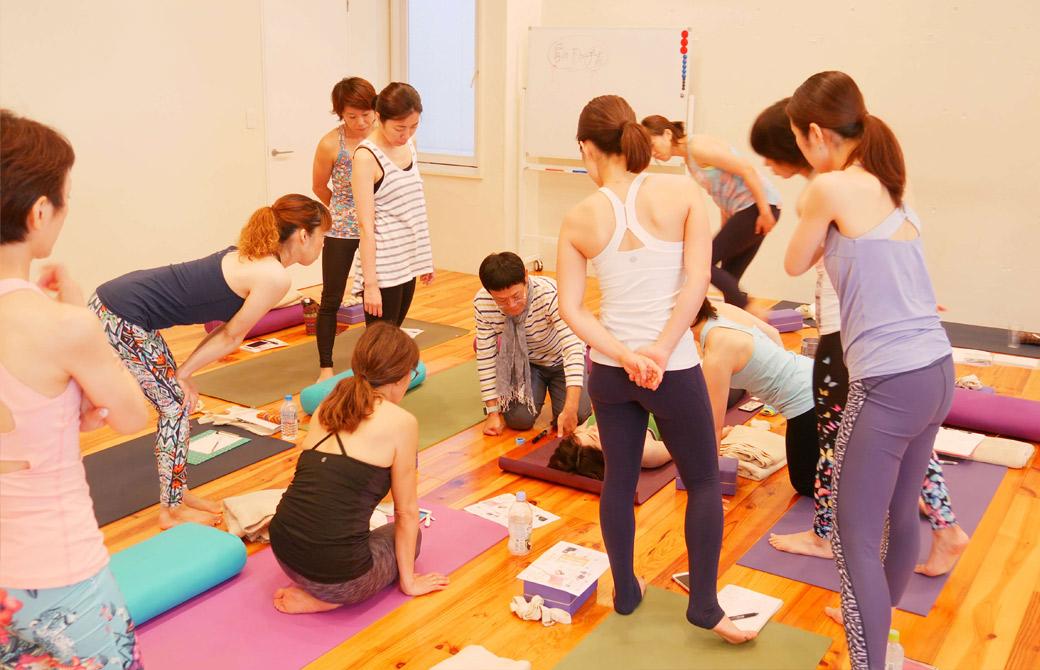 内田かつのり先生がマットに横になっている生徒さんをモデルにして説明している様子