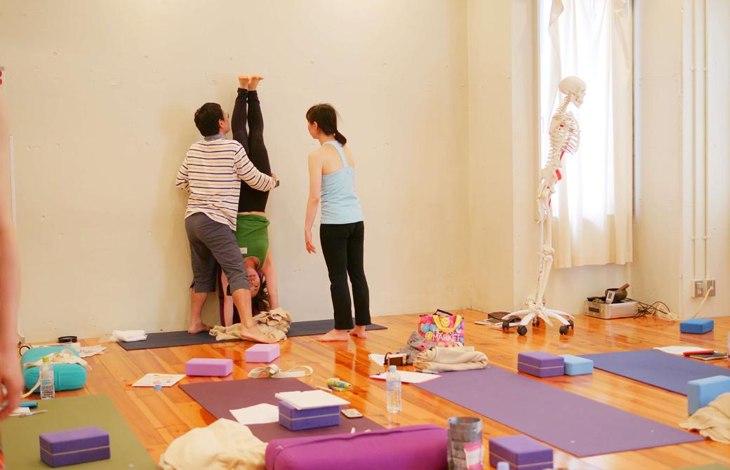 壁を背にして逆立ちしている生徒さんを支える内田かつのり先生