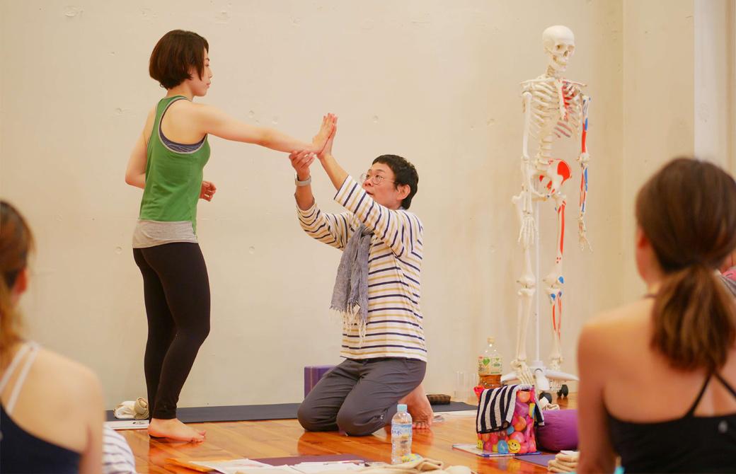 内田かつのり先生が生徒さんと手と手を合わせて、手首の力の入れ方を説明している様子