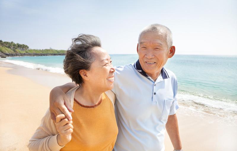 海辺を歩く高齢者夫婦