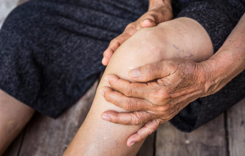 高齢者が膝を手で押さえている