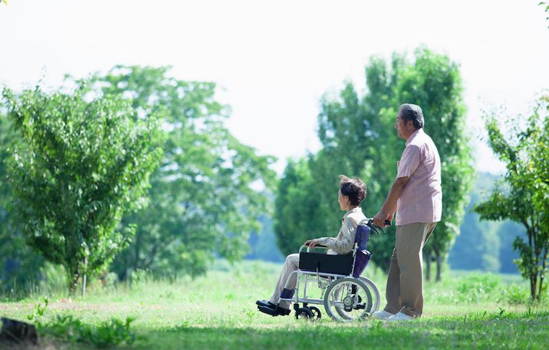 散歩中、立ち止まっている車椅子の高齢者