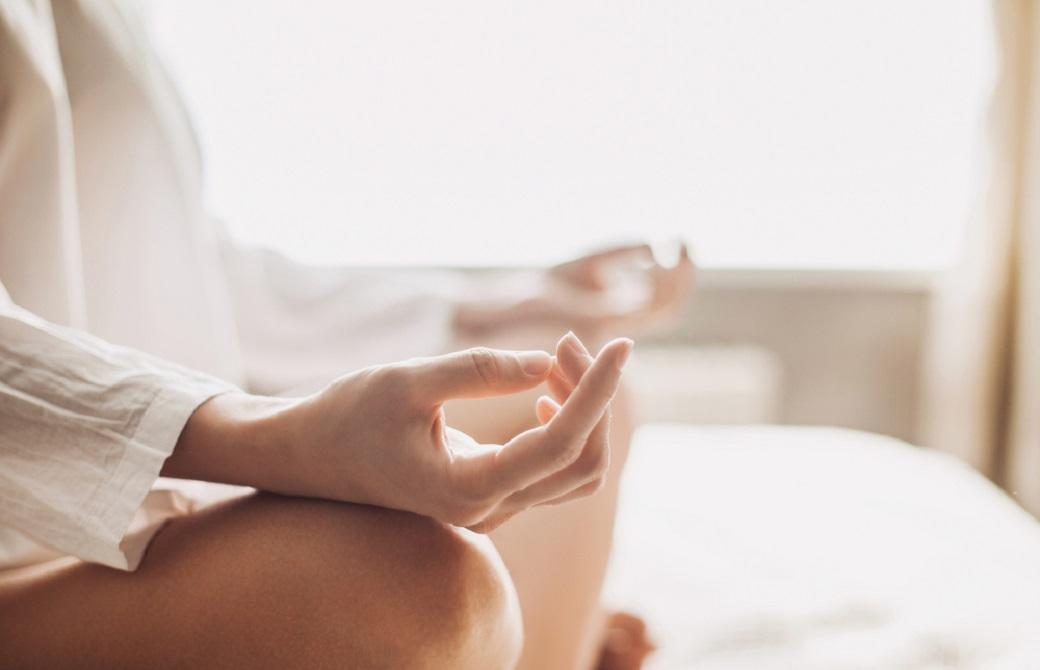 あぐらを組み、ひざの上に手をのせて瞑想する女性