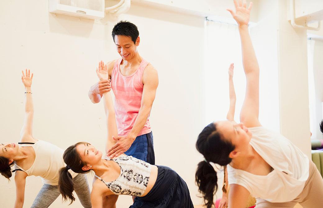 ヨガインストラクター浅野佑介先生が西畑亜美先生のトリコナアーサナをアジャストしている