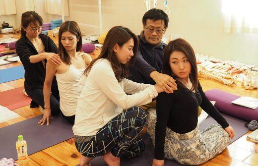座った状態で後方に体をねじる女性をアジャストする女性と内田かつのり先生