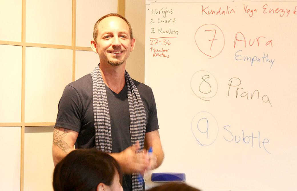 笑顔でヨガ数秘学の講義をするタイラー・モンガン