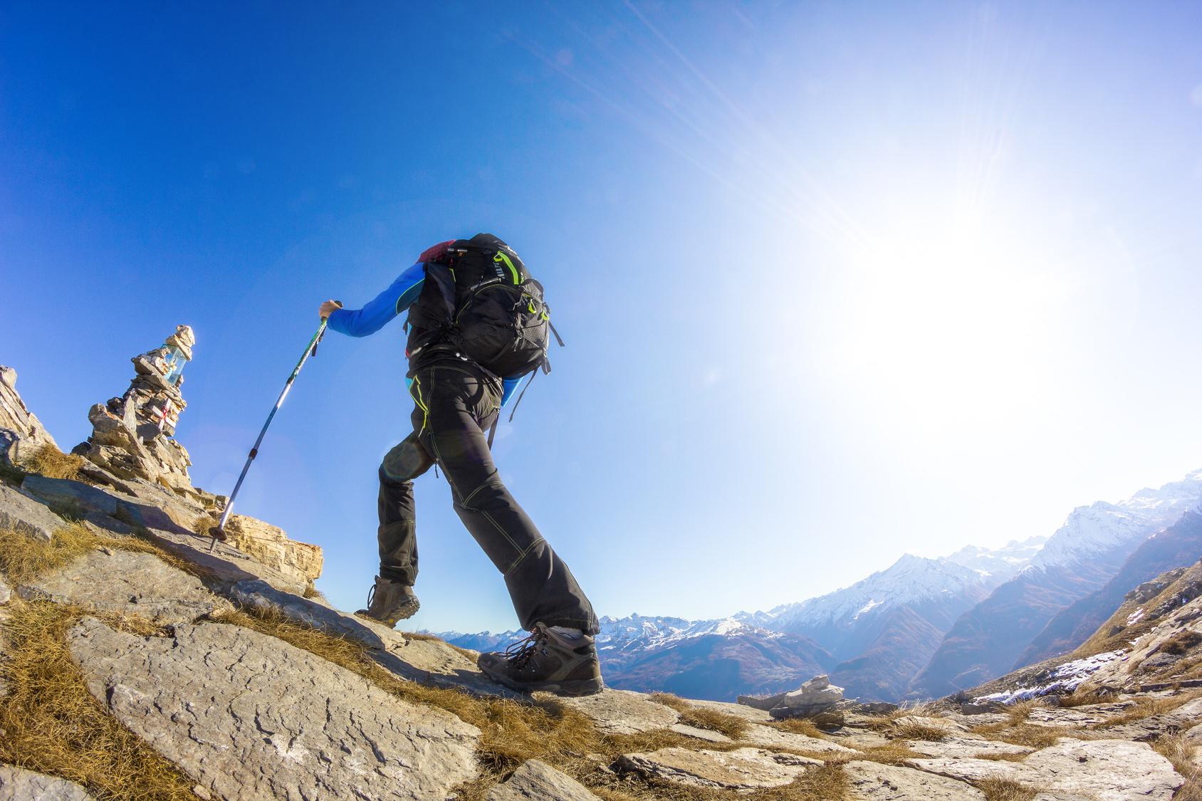青空の下、登山をしている男性。