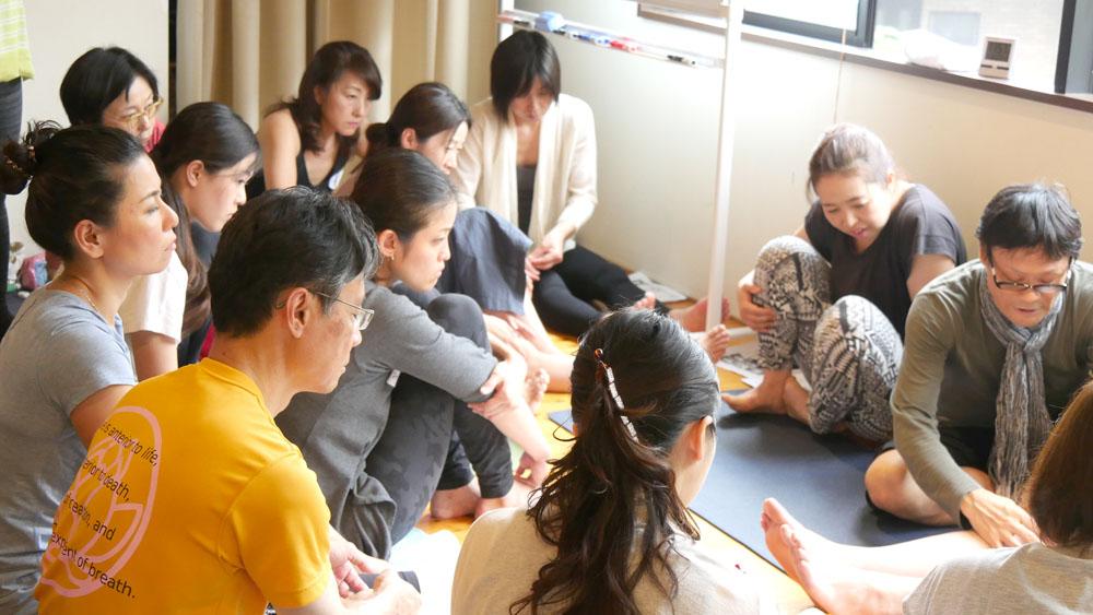 ヨガ解剖学講師内田かつのり先生による膝関節セラピーの様子。生徒さんを例にして、膝の怪我について説明する内田先生