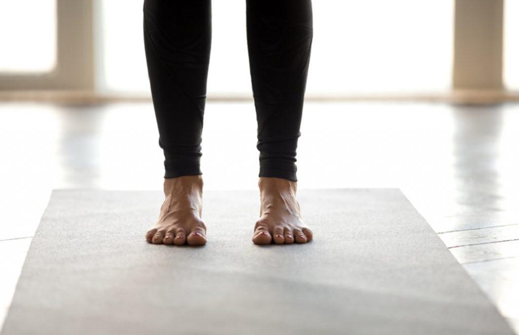 ヨガマットの上に立つ女性の足足元