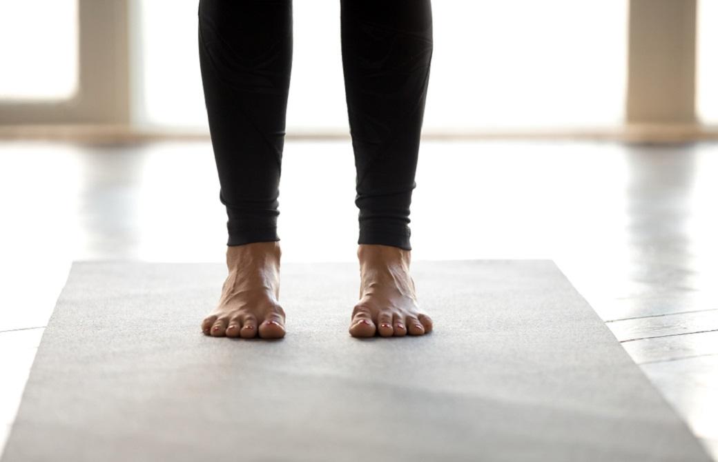 ヨガマットの上に立つ女性の足元
