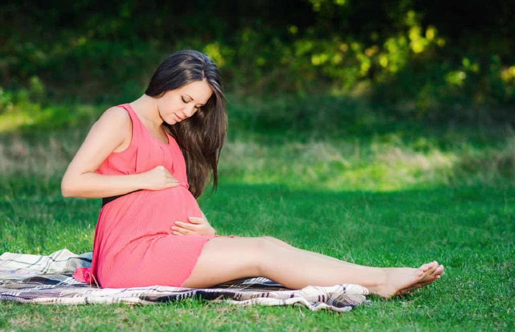 芝生にシートを広げてその上に座っている妊婦さん