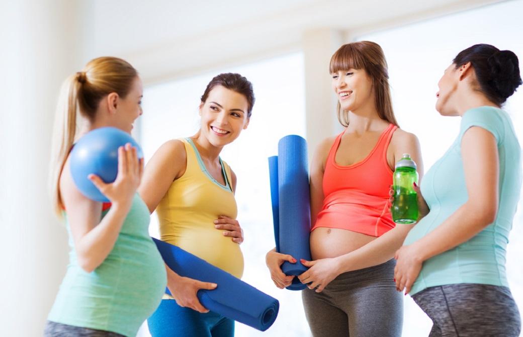 4人の妊婦さんがヨガマットを持って立ち話している