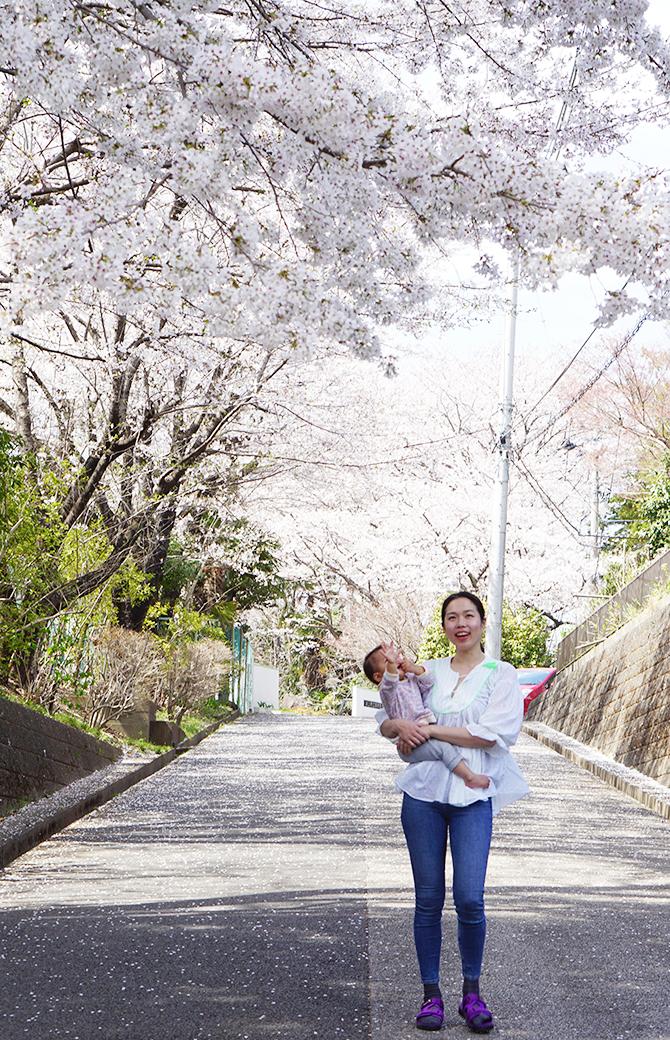 佐久間涼子先生が娘さんをだっこして桜の木の下に立っている