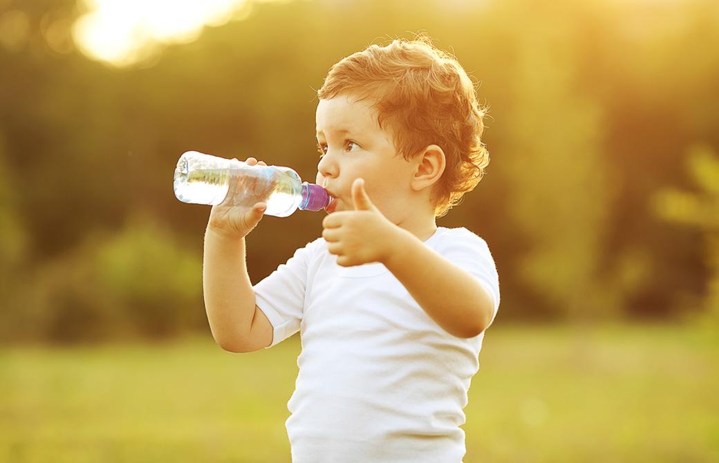 哺乳瓶に入った水を飲む子供