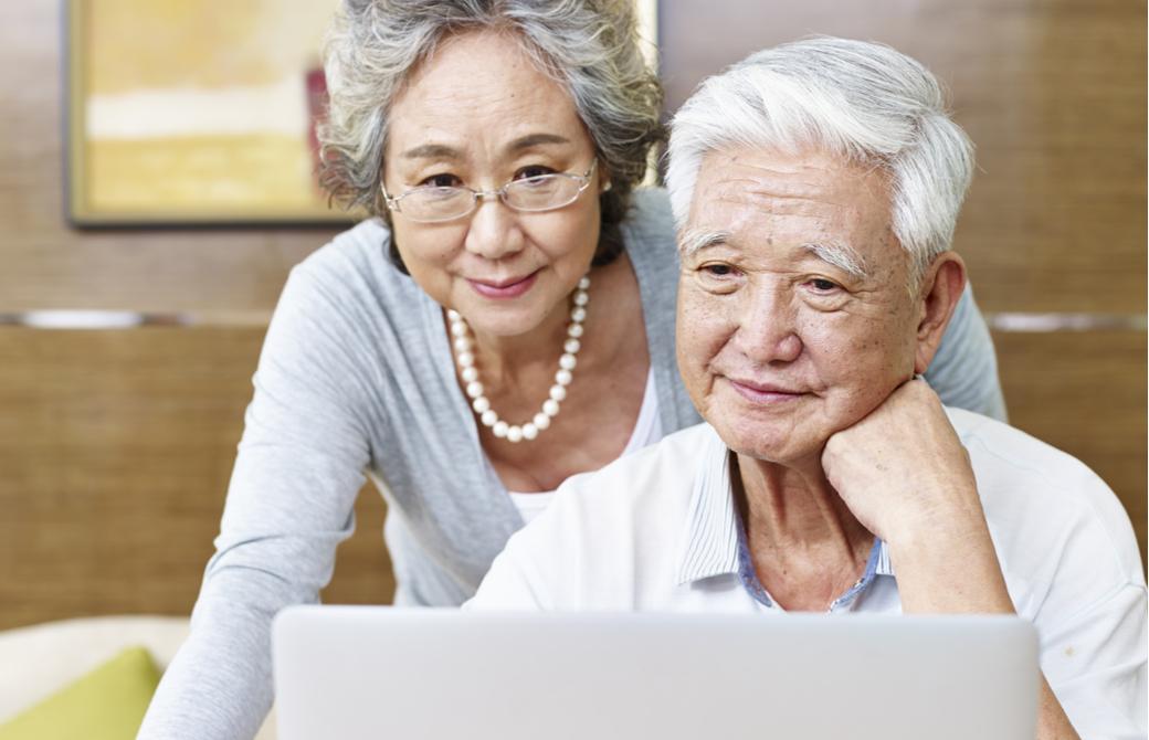 シニア夫婦がパソコンで作業をしている様
