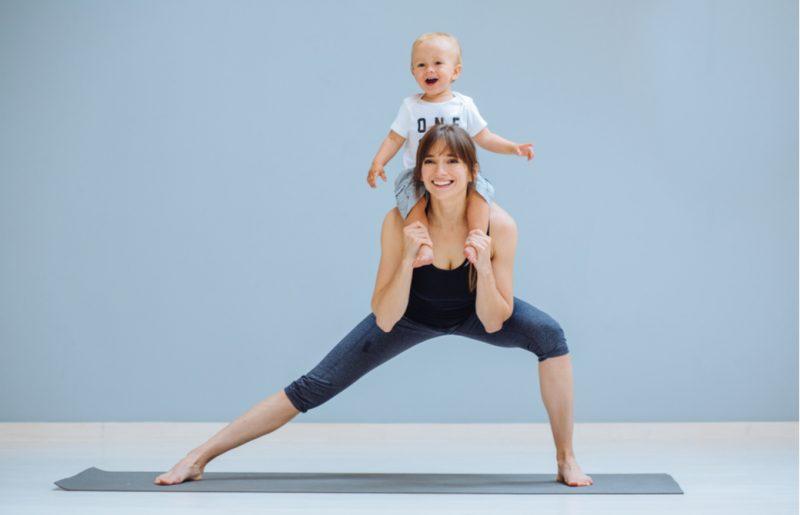 赤ちゃんを肩車しながらヨガをする女性