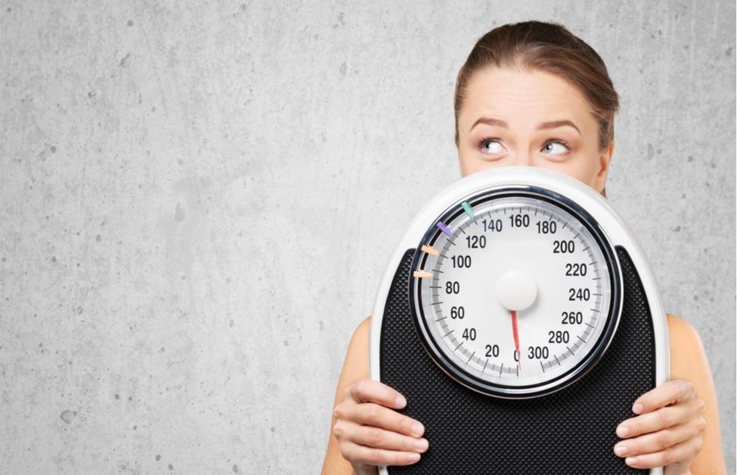 体重計を持って考える女性