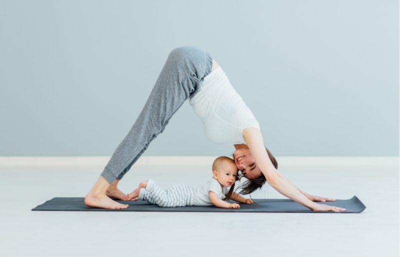 ダウンドッグをしている母親と下をくぐる赤ちゃん
