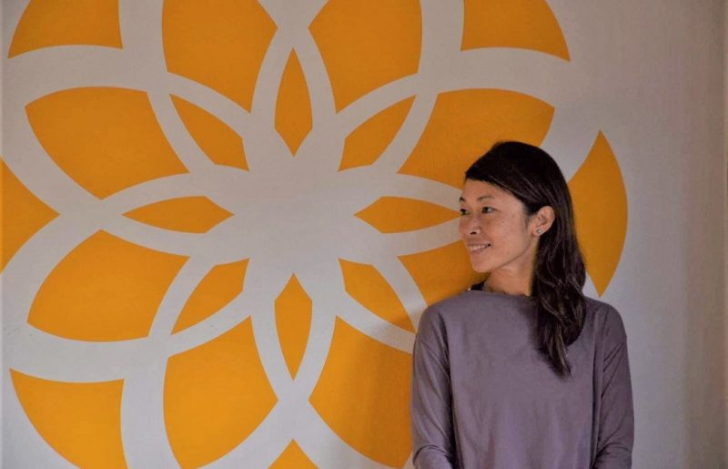 semperviva yoga studioの黄色い花模様の壁の前で横を向いて微笑むマイコ先生