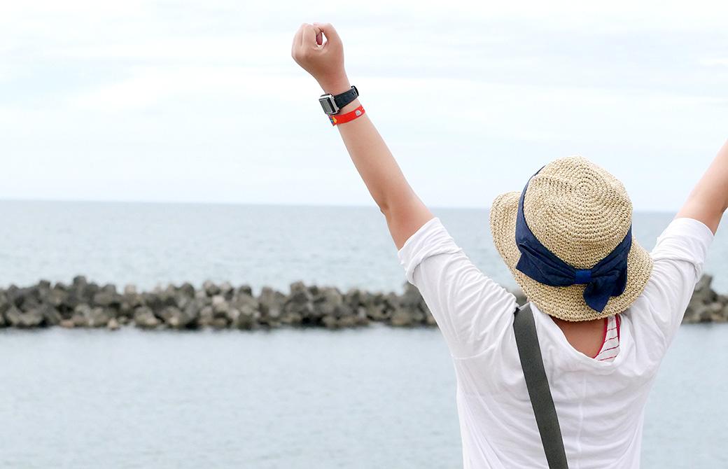 ヨガスパ近くの海に向かって両腕を上げている亀井さん