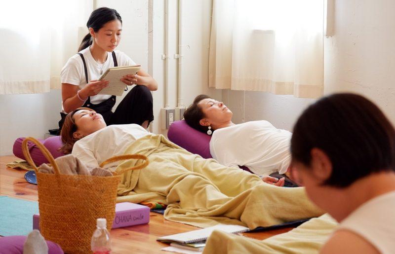 目を閉じて横になる2人の生徒さんとノートを読む指導者役の生徒さん