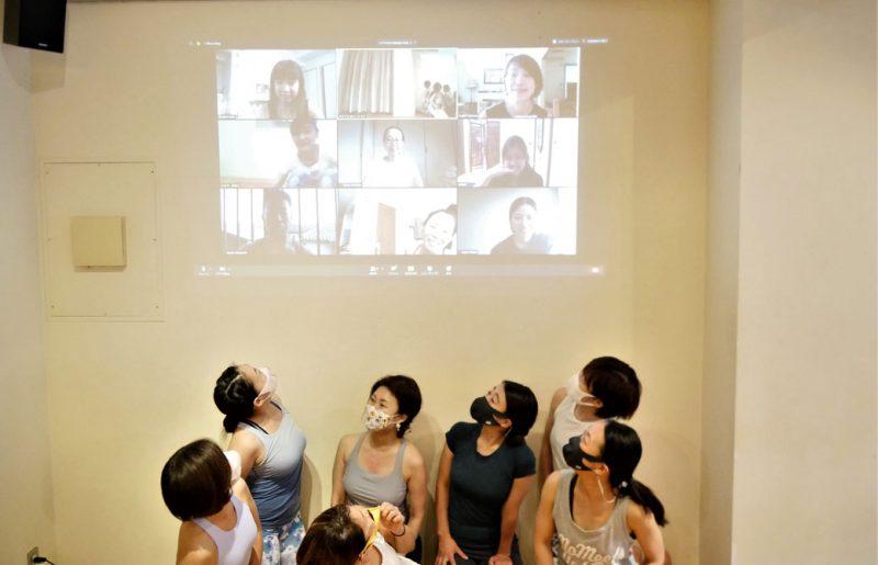 壁に映る画面の向こうの生徒さんと、対面で受講している生徒さん
