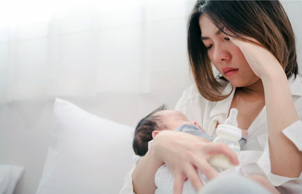 赤ちゃんをだきながら頭を抱える母親