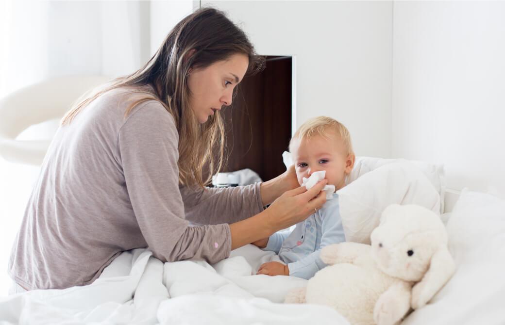 子供の鼻を噛んであげている母親