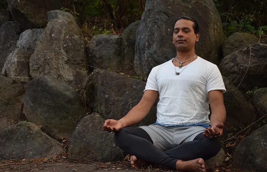 グルジが岩の前で瞑想している様子