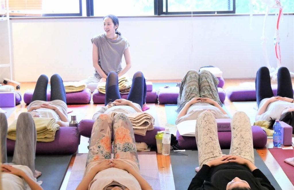 寝て膝を立てているたくさんの生徒さんと、座っているサントーシマ香先生