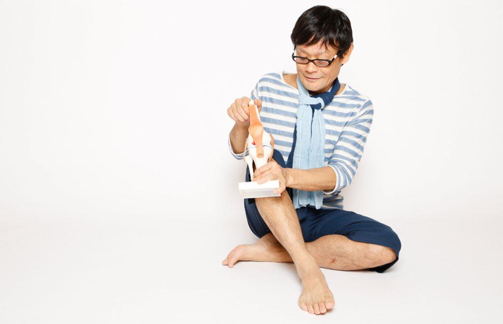 内田かつのり先生が膝の模型を持って座っている